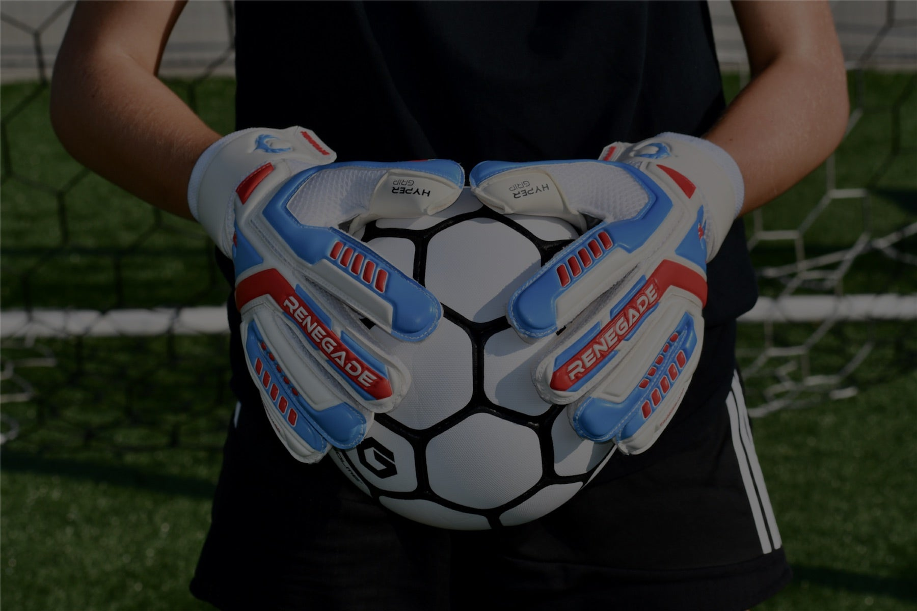 goalie holding the ball with 2 hands while wearing soccer gloves for goalkeepers