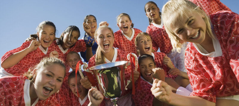 all girls soccer team holding their trophy together
