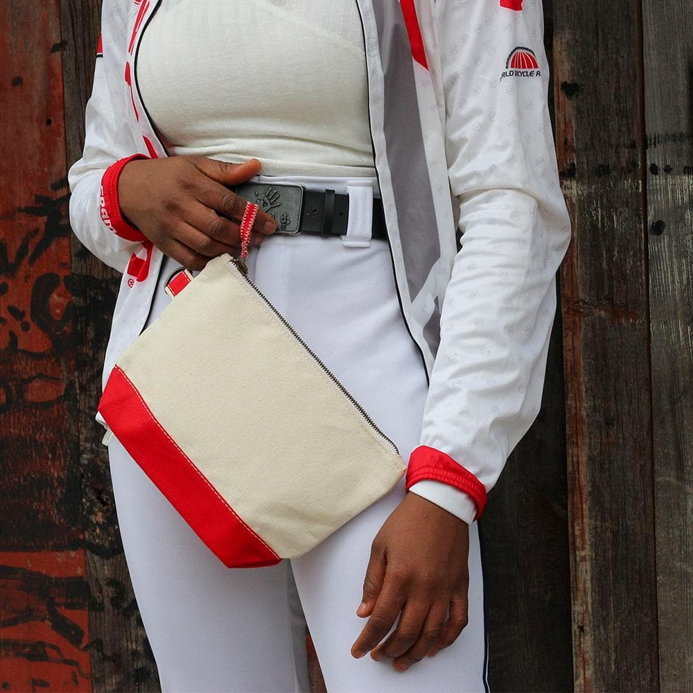 Model holding the All In Pouch from ShoreBags. Heavyweight canvas zippered pouches with an all natural body and a colored canvas bottom and pull tab. Includes an antiqued brass d-ring for each attachment.
