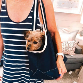 Model and her dog in the heavyweight canvas tote for dogs with outside pocket and long striped comfortable shoulder straps.