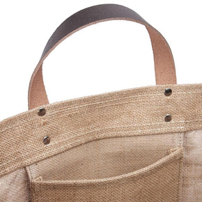 Close up photo of the Bazaar Tote from ShoreBags printed with the words Fresh and Local, made from all-natural jute with natural canvas trim and leather handles. This bag has a laminated interior and is made from sustainable materials.