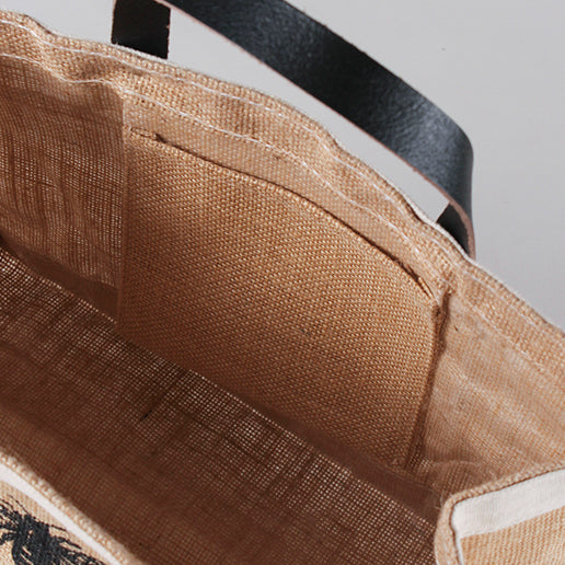 """Detail picture of Jute and leather small tote from ShoreBags featuring a laminated interior and a printed message Bees and Trees on the front side."""