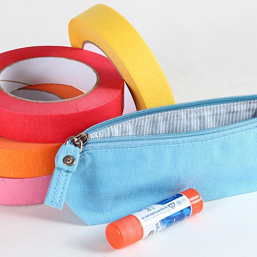 """Light blue pencil pouch shown with a glue stick and a stack of colorful masking tape."""