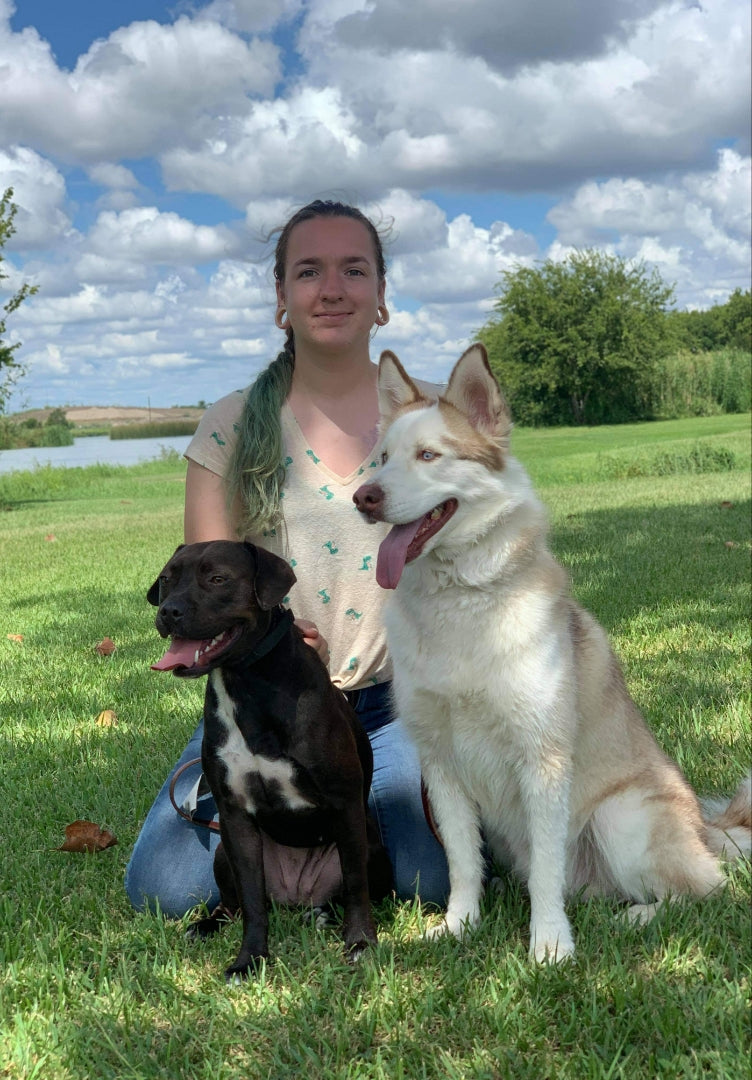 Becca sitting with her two dogs