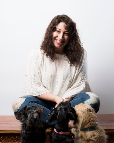 Founder Jen Mello seated on bench with her three dachshunds begging for treats