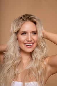 A picture of Lauren Burnham Luyendyk fluffing her hair in a portrait studio against a brown background