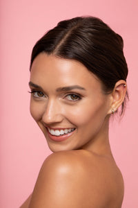 A picture of Whitney Fransway with natural makeup and an updo against a pink background.