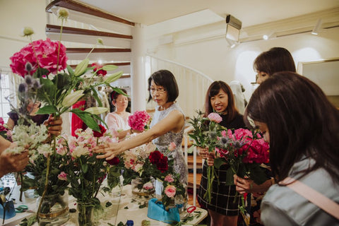 Participants selecting flowers and arranging them together into an elegantly designed flower bouquet.