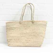 A practical and stylish must-have fashion accessory, perfect for carrying books or a laptop. The Santorini Tote Basket is a contemporary flat basket with a pleated handle, handwoven using natural palm leaf. Ethically Handmade in Morocco