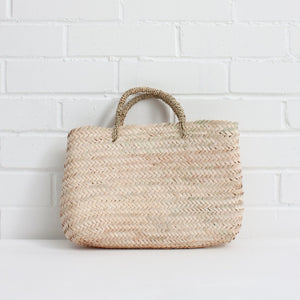 The Tokyo Shopper Basket is a purse style shopping basket with a rectangular shape for a minimalist feel. The basket bag is handwoven by Moroccan artisans using natural palm leaf with a rolled palm leaf handle.