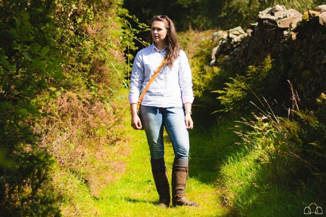 Woman wearing country style striped shirt, jeans and country boots