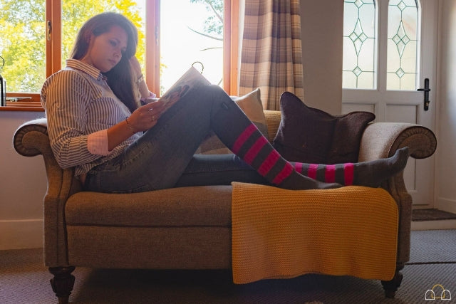 Woman sitting on settee wearing navy striped shirt, jeans and striped socks in pink and grey