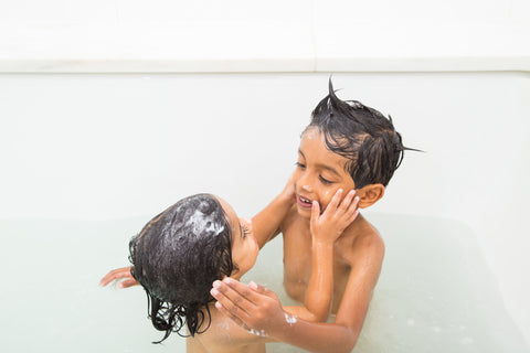 Two kids putting lotion on each other during bathtime