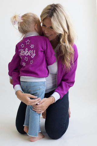 mom hugging daughter on her knees wearing a purple jacket that matches her daughters