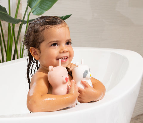 Little girl in bathtub holding Bubbsi shampoo and body cream bottles
