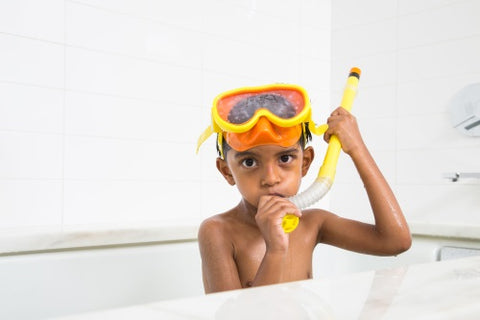 boy wearing orange and yellow snorkel mask in bathtub