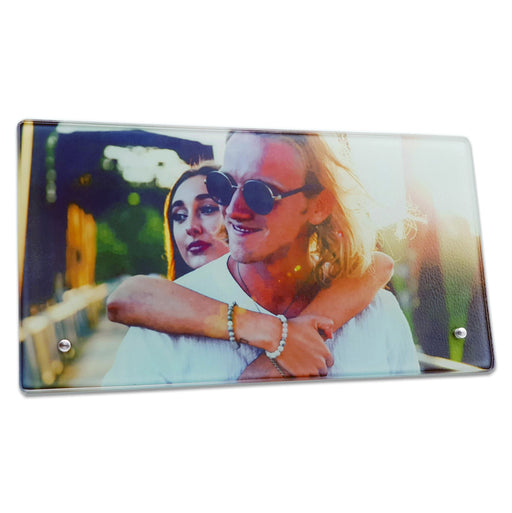 Landscape glass photo block printed with a selfie of a couple while she hugs him behind his shoulders