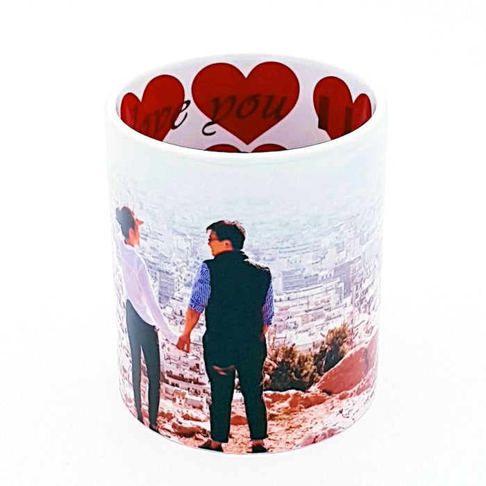 White mug printed on the inside with red hearts and I love you message the outside is personalised with couple holding hand on top of a hill with city view