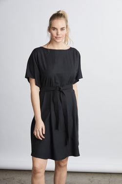 woman wearing a black raw silk noil belted knee length dress