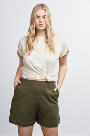 woman wearing green raw silk noil high waisted shorts and white tee shirt