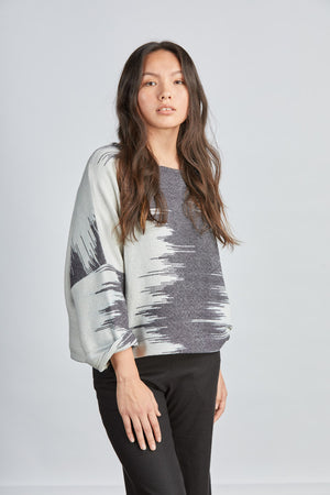 woman wearing a blue and white patterned hand woven oversized sweater with black pants