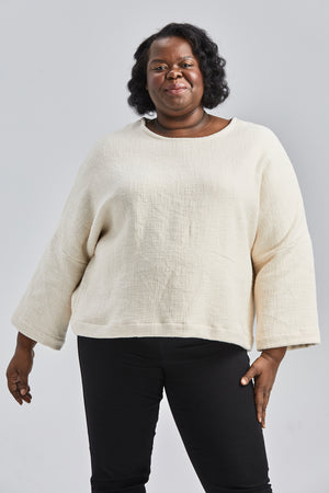 woman wearing a size medium handwoven cream sweater with black pants