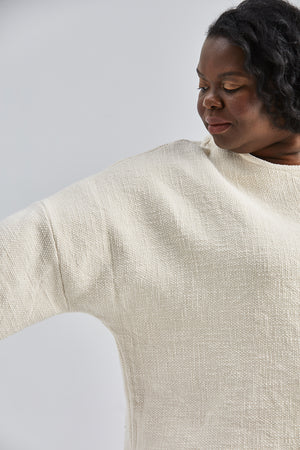 woman wearing a size small handwoven cream sweater with black pants