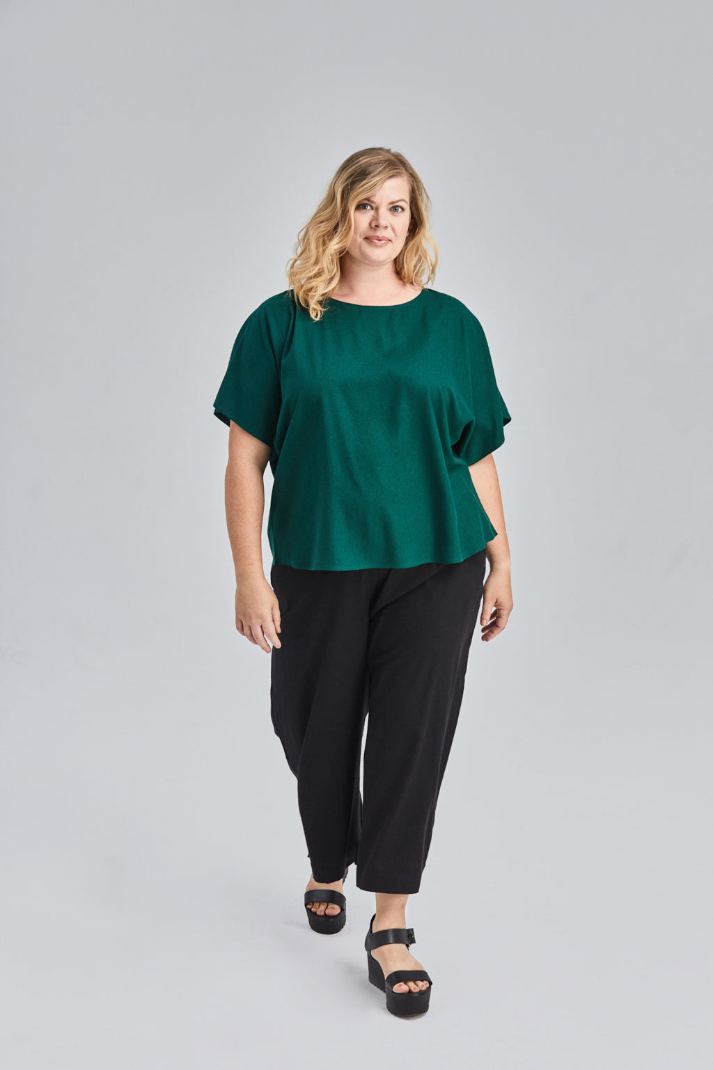 size 2XL woman wearing a green flowy raw silk noil blouse and black pants