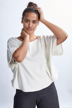 model wearing a white flowy raw silk noil blouse and black pants