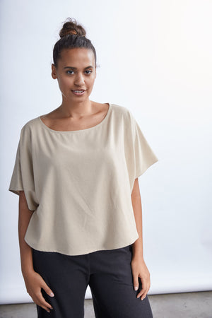 woman wearing a brown flowy raw silk noil blouse and black pants
