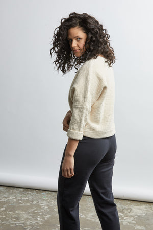 size 3XL woman wearing a handwoven cream sweater with black pants