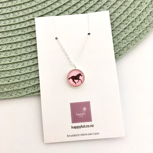 Girls horse necklace on a pink background, glass dome pendant with silver link chain