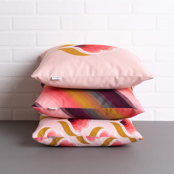 tullibee margot in the middle large retro floral cushion, agnes cushion & margot all over print cushion stacked on top one another on a concrete floor in front of a white brick wall