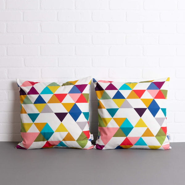 two tullibee Yoshi triangle geometric rainbow colour cushions sat side by side on a concrete floor in front of a white brick wall