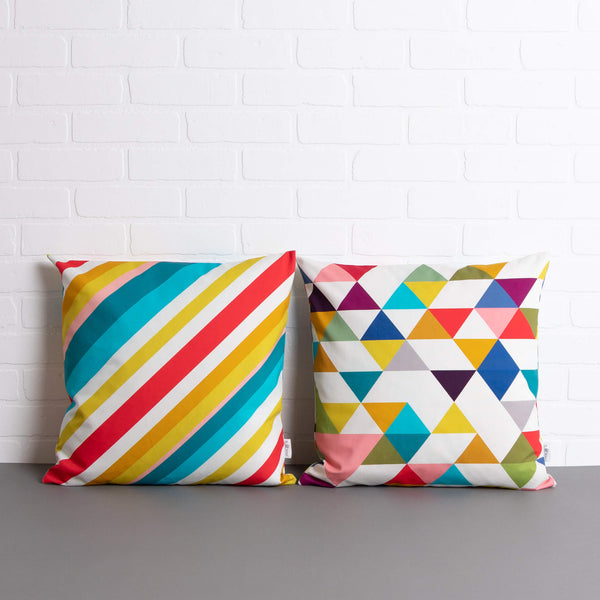 tullibee milo retro diagonal varying width stripe cushion & Yoshi triangle geometric cushion sat side by side on a concrete floor in front of a white brick wall