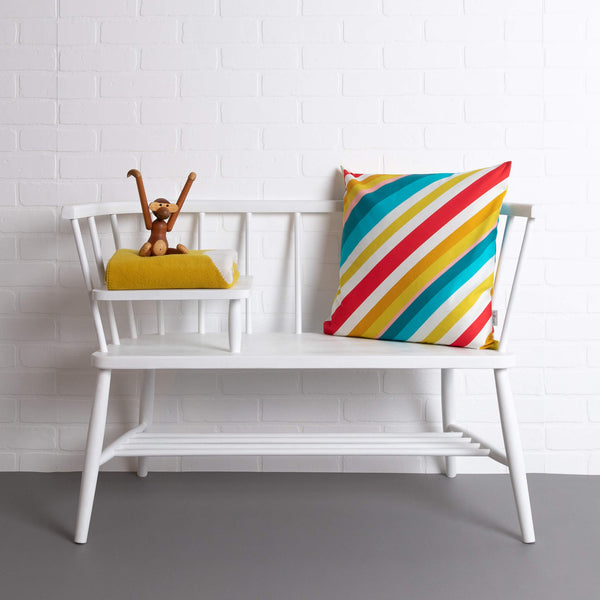 tullibee milo retro diagonal varying width stripe cushion in tones of aqua, red, pink, mustards & white colours on a white ercol telephone bench along with a tullibee picalilli knitted blanket & wooden monkey.   In front of a white brick wall