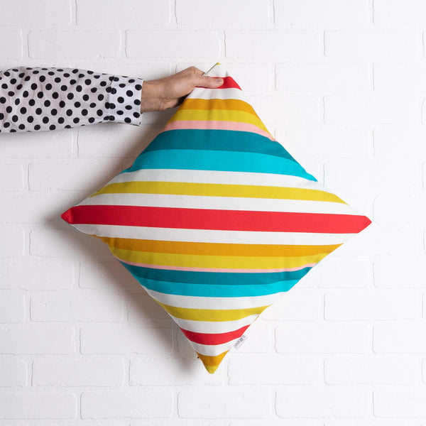 tullibee milo retro diagonal varying width stripe cushion in tones of aqua, red, pink, mustards & white colours being held out by an arm with a black & white spotty shirt