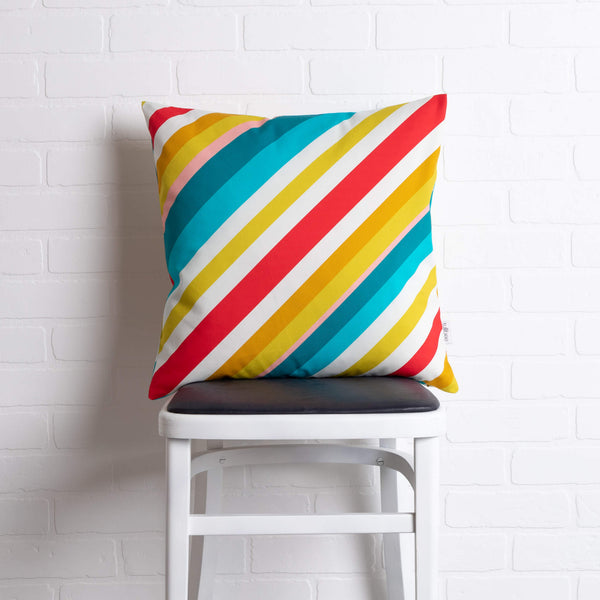 tullibee milo retro diagonal varying width stripe cushion in tones of aqua, red, pink, mustards & white colours sat on a stool in front of a white brick wall