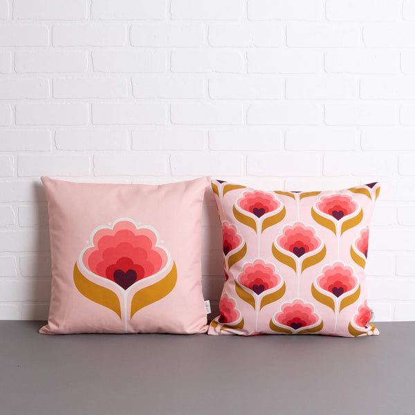 tullibee margot in the middle large retro floral cushion & margot all over print cushion sat side by side on a concrete floor in front of a white brick wall