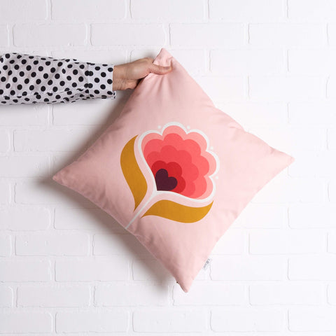 tullibee margot in the middle large retro floral cushion, in cherry flamingo & mustard colours being held out by a arm with a black & white spotty shirt