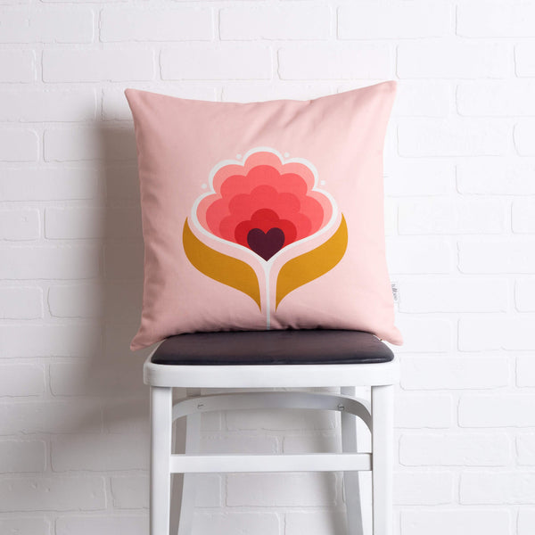 tullibee margot in the middle large retro floral cushion, in cherry flamingo & mustard colours sat on a stool in front of a white brick wall