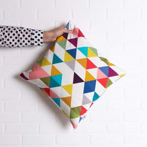 tullibee yoshi triangle geometric rainbow colour cushion being held out by an arm with a black & white spotty shirt
