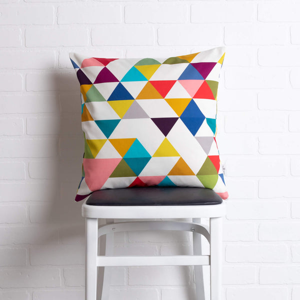 tullibee yoshi triangle geometric rainbow colour cushion sat on a stool in front of a white brick wall