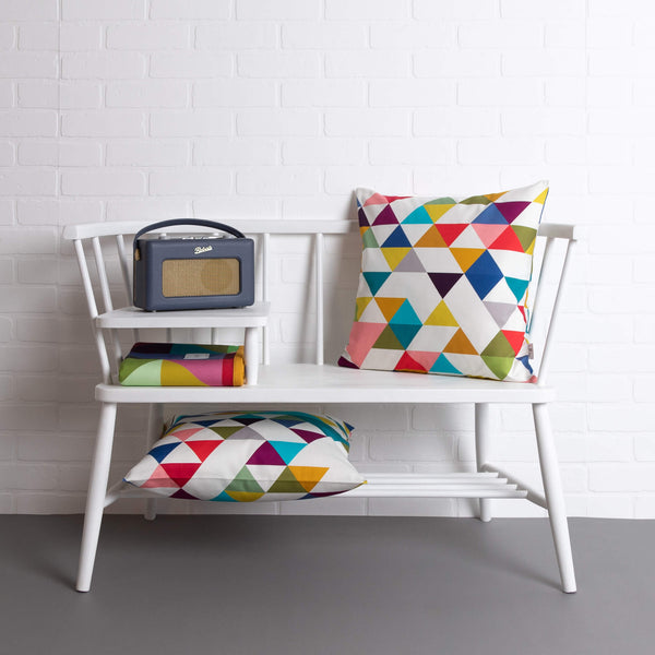 tullibee Yoshi rainbow triangle geometric print cushion on a white ercol telephone bench along with a second Yoshi cushion under bench, colourful tullibee blanket & Roberts retro style radio.   In front of a white brick wall