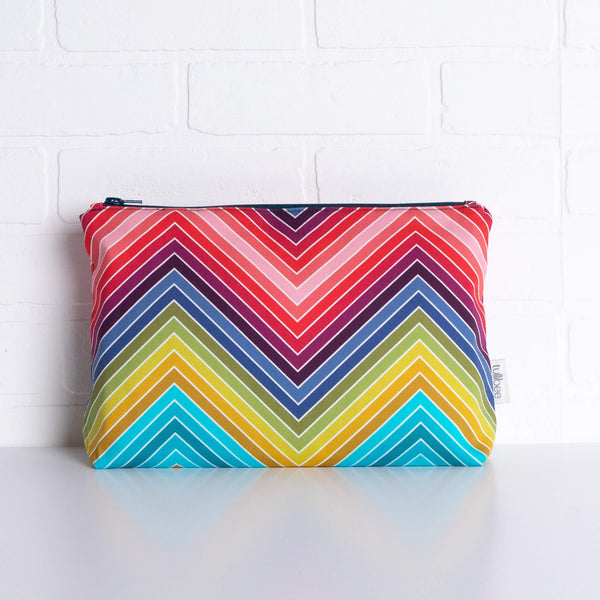 tullibee marni rainbow zig-zag maxi pouch in front of a white brick wall (front view)