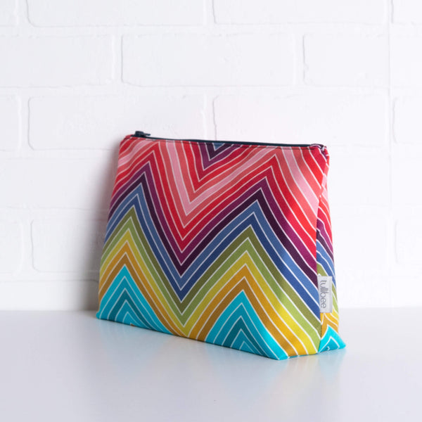tullibee marni rainbow zig-zag maxi pouch in front of a white brick wall at an angle to show the depth of the pouch & gusset