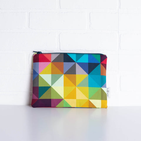 tullibee jules rainbow geometric triangle midi rectangular pouch propped against a white brick wall (front view)