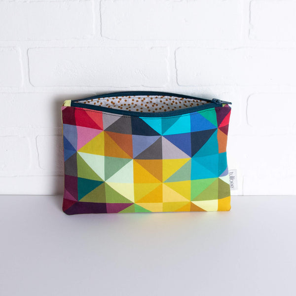 tullibee jules rainbow geometric triangle midi rectangular pouch propped against a white brick wall with zip top open & view of mustard spot lining