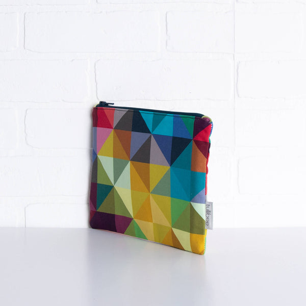 tullibee jules rainbow geometric triangle midi rectangular pouch propped upright against a white brick wall at an angle to show the depth of the pouch