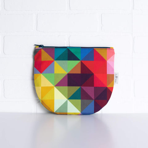 tullibee jules rainbow geometric triangle midi round pouch propped against a white brick wall (front view)